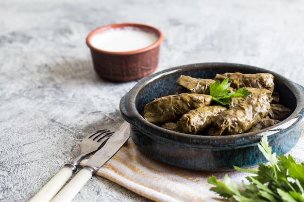 Dolma traditionnel (sarma) dans les feuilles de vigne avec fond. liban cuisine turque grecque du moyen-orient. dîner alimentaire dolmadakia