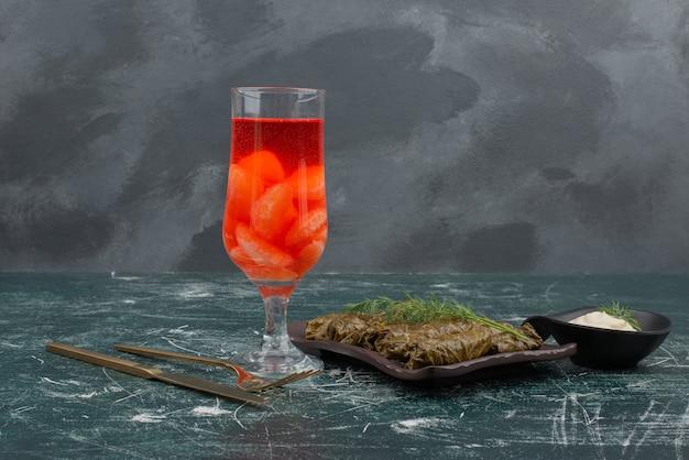 Dolma avec verre de jus et crème sure sur table en marbre.
