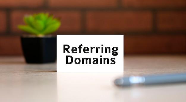 Domaine de référence pour le référencement - texte du concept d'entreprise sur la liste blanche et avec un stylo et un pot noir avec une fleur derrière