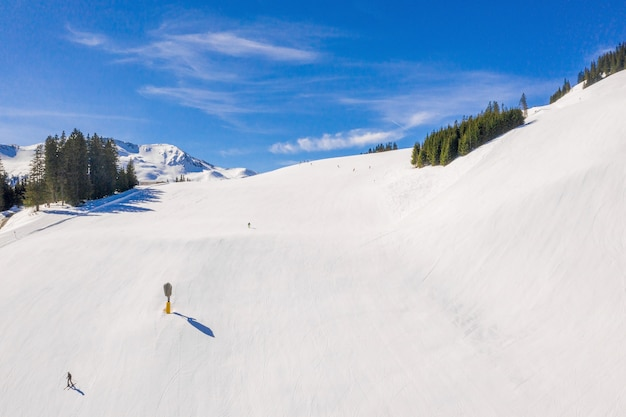 Domaine skiable avec des skieurs glissant sur la pente enneigée sous un ciel bleu