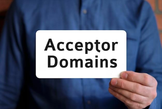 Domaines accepteurs - texte sur un panneau blanc dans la main d'un homme en chemise bleue