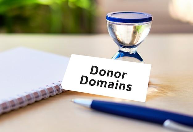 Domaines de donateurs - texte de concept d'entreprise seo sur un ordinateur portable blanc et horloge sablier, stylo bleu, feuilles vertes de fleurs