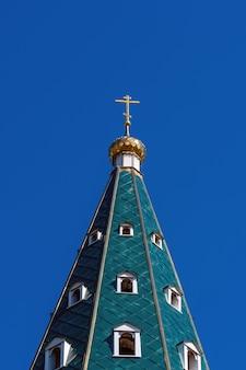 Dôme doré avec une croix sur le toit vert d'une église