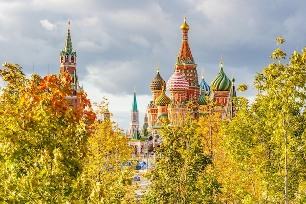 Dômes aux couleurs vives de la cathédrale saint basile sur la place rouge contre le ciel d'automne avec des nuages gris et des arbres dorés en journée ensoleillée