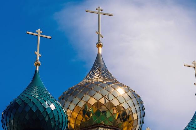 Dômes dorés brillants et verts avec croix sur l'église orthodoxe chrétienne