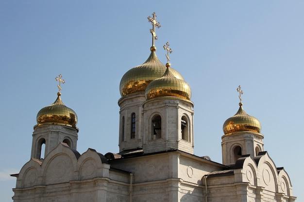 Dômes dorés de l'église orthodoxe contre le ciel bleu.