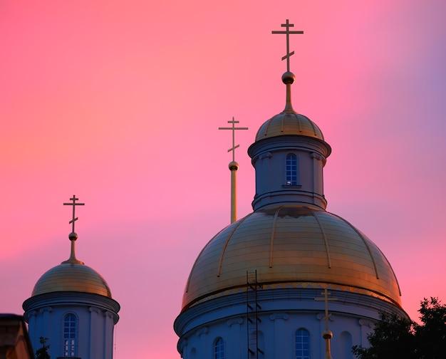 Dômes de temple d'or pendant le coucher du soleil rose