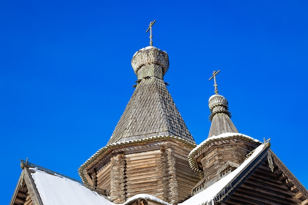 Les dômes d'une vieille église en bois sur fond de ciel bleu clair, la période de l'année est l'hiver