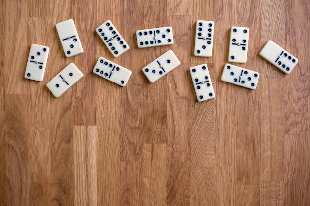 Dominos blancs sur fond de bois vue de dessus lieu de jeu de société pour texte