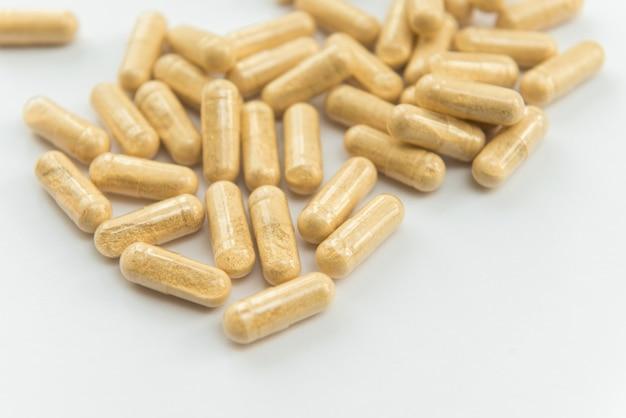 Dommages médicinaux dans des capsules sur fond blanc, mise au point sélective. santé et pharmacie.