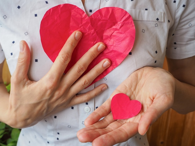 Don de coeur. grand et petit coeur rouge dans sa main.