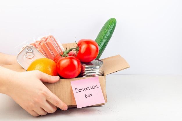 Don ou livraison de nourriture à domicile, les mains donnent ou prennent une boîte en carton avec de la nourriture