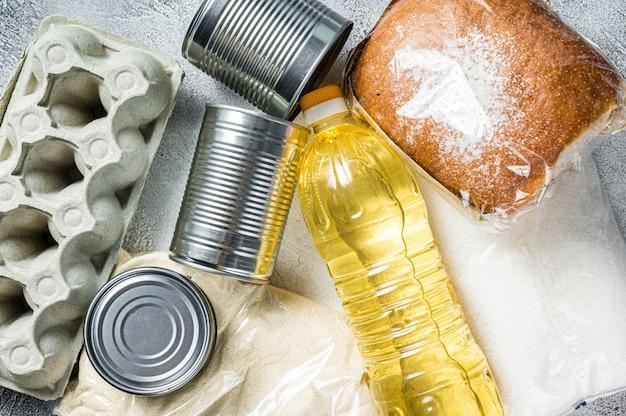 Don de produits alimentaires, concept d'aide à la quarantaine. huile, conserves, pâtes, pain, sucre, œuf. fond blanc. vue de dessus.
