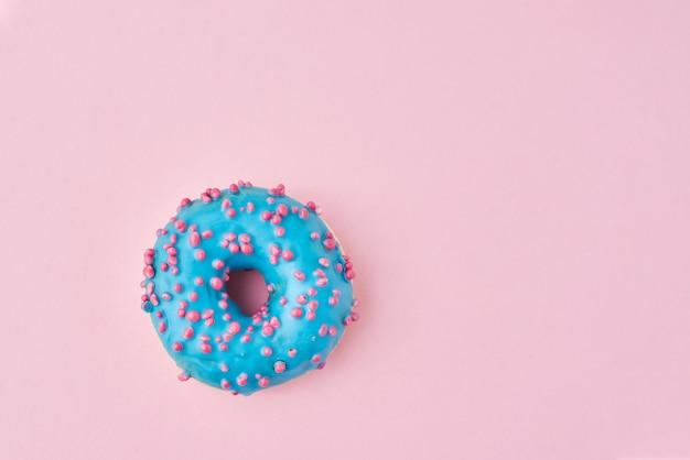 Donat bleu décoré de paillettes et de glaçage sur la surface rose. concept alimentaire créatif et minimalis, vue de dessus à plat