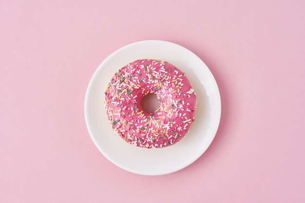 Donat décoré de paillettes et de glaçage en plaque blanche sur fond rose. concept alimentaire créatif et minimalis, vue de dessus à plat