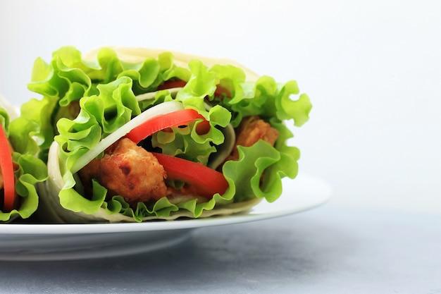 Doner kebab sur une assiette blanche. shawarma avec viande, oignons, salade et tomate sur fond gris.