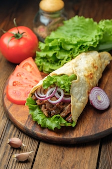 Doner kebab est allongé sur la planche à découper. shawarma avec viande, oignons, salade est allongé sur une vieille table en bois blanche.