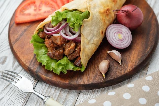 Doner kebab est allongé sur la planche à découper. shawarma avec viande, oignons, salade repose sur une vieille table en bois sombre.