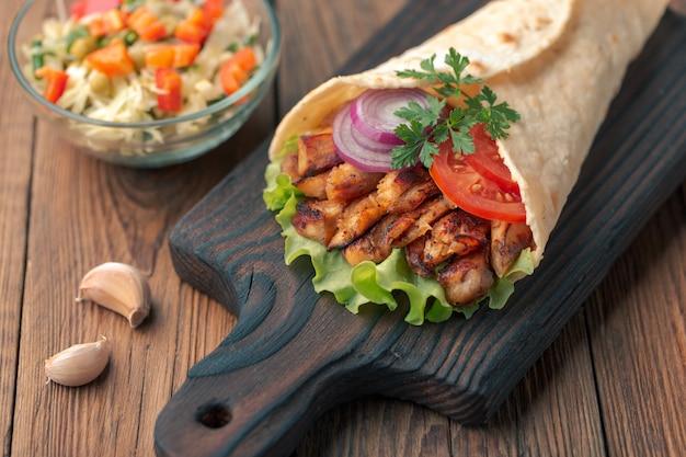 Doner kebab est allongé sur la planche à découper. shawarma avec de la viande de poulet, des oignons, de la salade repose sur une vieille table en bois sombre.