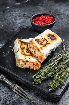 Doner kebab roll dans un lavash avec du poulet et de la viande de bœuf.