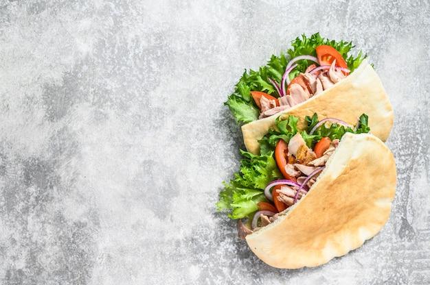 Doner kebab avec viande de poulet grillée et légumes dans du pain pita.