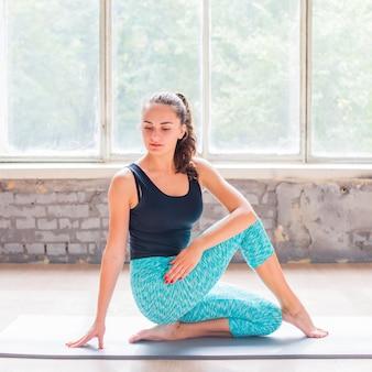 Dong yoga de belle jeune femme sur tapis d'exercice
