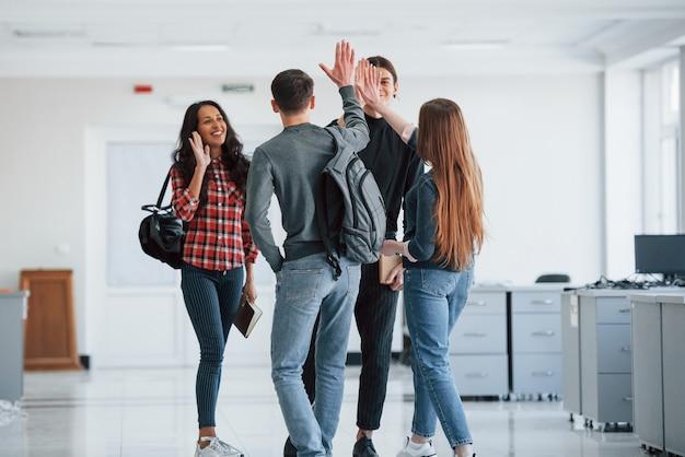 Donner cinq. groupe de jeunes marchant dans le bureau à leur pause