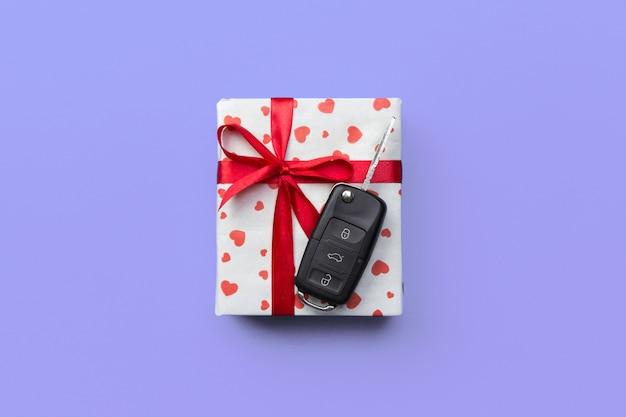 Donner le concept de clé de voiture cadeau sur fond coloré violet