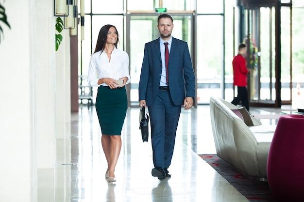 Donner des conseils aux entreprises. collègues d'affaires interagissant les uns avec les autres tout en marchant dans le couloir au bureau