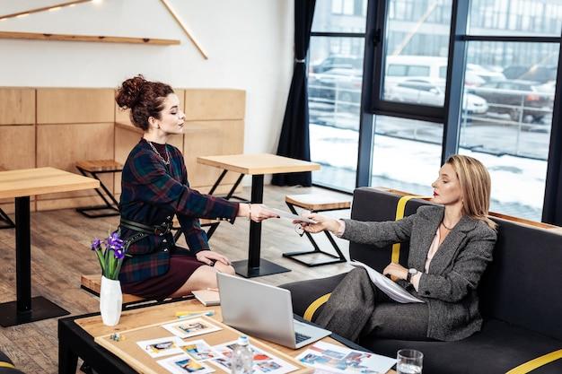 Donner un cv. secrétaire professionnelle élégante et bouclée donnant son cv à une femme d'affaires prospère
