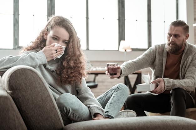 Donner de l'eau. thérapeute barbu attentionné donnant un verre d'eau à une fille qui pleure pendant la thérapie