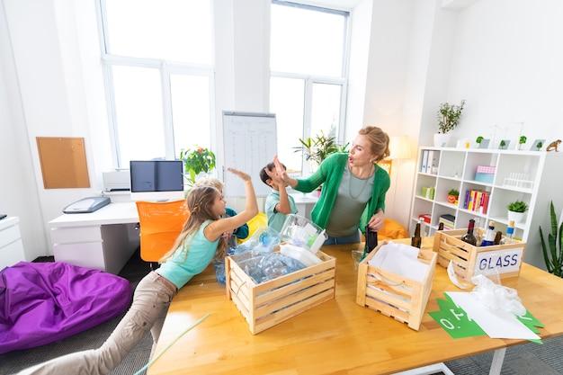 Donner un high five. professeur aux cheveux blonds cool moderne donnant cinq à ses élèves après le tri des déchets