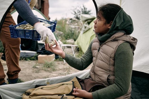 Donner de la nourriture en conserve à une fille réfugiée