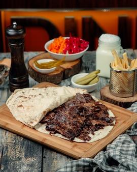 Donneur de viande au lavash avec des cornichons marinés et des frites.
