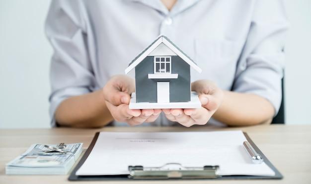 Donnez un agent immobilier, tenez le modèle de maison et expliquez le contrat commercial, le loyer, l'achat, l'hypothèque, le prêt ou l'assurance habitation.