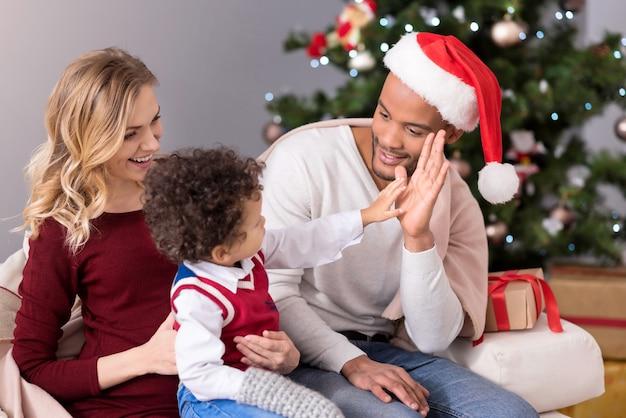 Donnez-moi un cinq. joli garçon sympa positif tenant son bras et regardant son père tout en lui donnant un cinq
