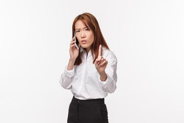 Donnez-moi une seconde, un instant. occupé à la femme d'affaires sérieuse ayant une conversation sérieuse au téléphone, montrant le doigt et demandant à quelqu'un d'attendre pendant qu'elle finit de parler, se lever