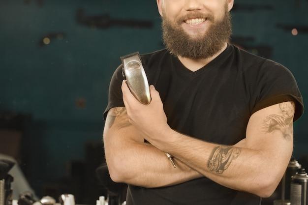 Ce dont la barbe a besoin. gros plan recadrée d'un barbier barbu et tatoué souriant tenant une tondeuse à la main
