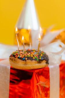Donut au chocolat sucré et bougies allumées sur un arrière-plan flou festif. notion de joyeux anniversaire.