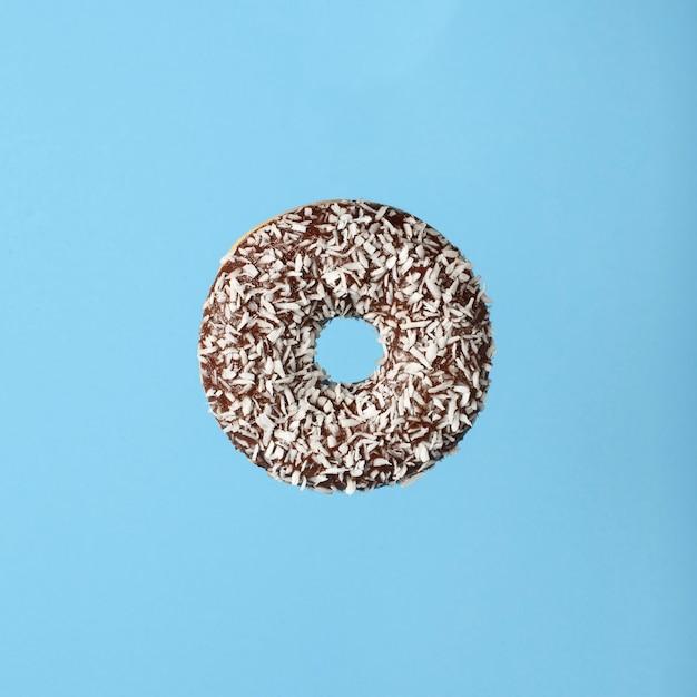 Donut au chocolat sucré volant sur fond bleu concept alimentaire