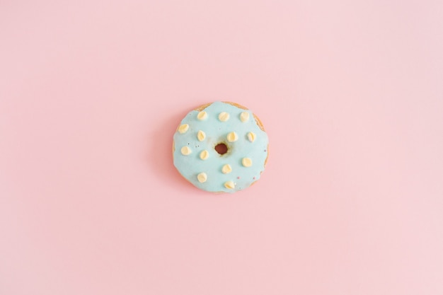 Donut bleu sur fond rose pastel