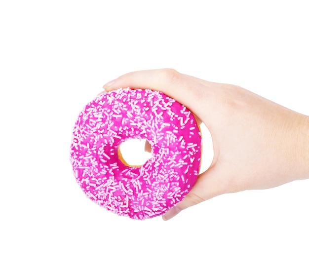 Donut dans une main féminine sur fond blanc