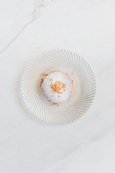 Donut décoré de vermicelles servi sur une table en marbre blanc