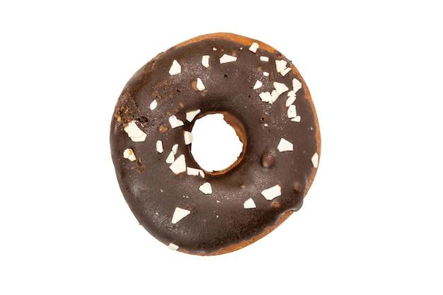 Donut en glaçage au chocolat saupoudré de morceaux de chocolat blanc isolé sur fond blanc