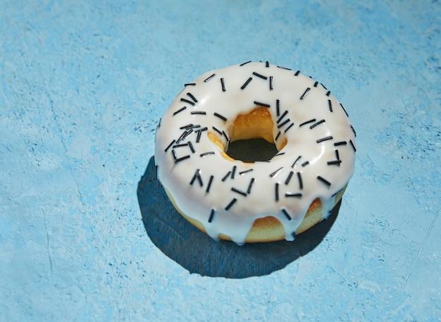 Donut avec glaçage blanc et arrose sur fond bleu.