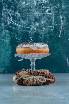 Donut glacé sur socle en verre au milieu d'une couronne de pin sur marbre.