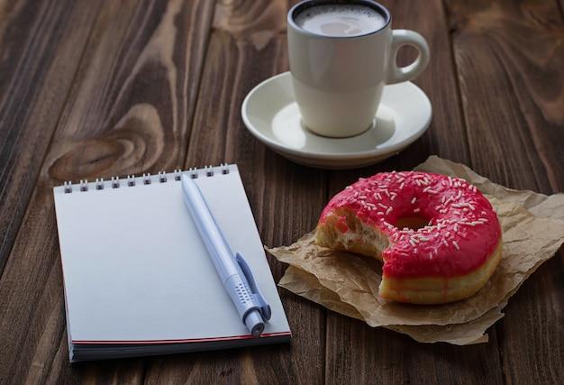 Donut mordu tasse de café et cahier