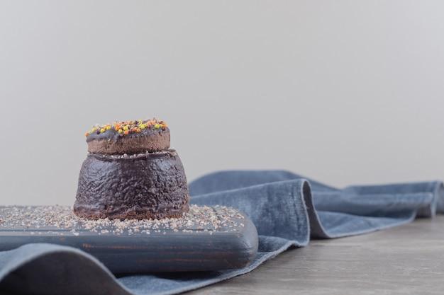Donut sur un petit gâteau au chocolat sur une planche sur marbre