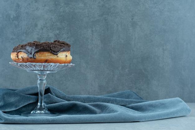 Donut sur piédestal en verre sur nappe froissée sur marbre.
