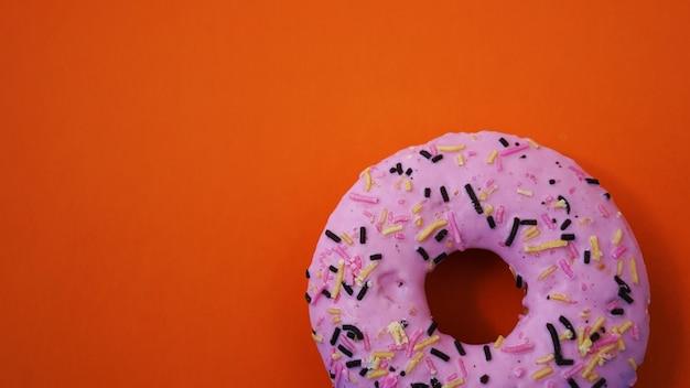 Donut rose doux sur fond orange - place pour le texte